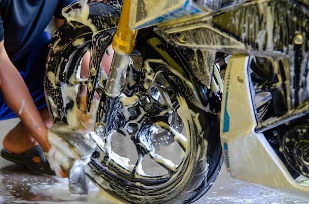 Mężczyzna Trzyma Gąbkę Do Mycia Kół Motocykla Premium Zdjęcia
