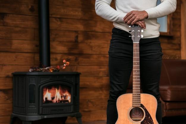Mężczyzna trzyma gitarę akustyczną Darmowe Zdjęcia