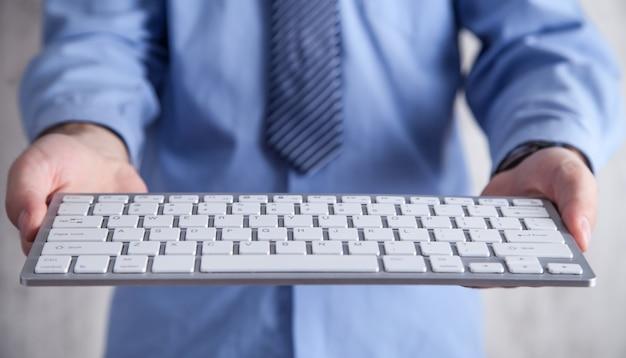 Mężczyzna Trzyma Klawiaturę Komputera. Technologia, Biznes Premium Zdjęcia
