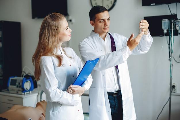 Mężczyzna Trzyma Kolbę Do Analizy Pielęgniarka Z Teczką W Ręku Słucha Lekarza Studenci W Szpitalnych Fartuchach Darmowe Zdjęcia