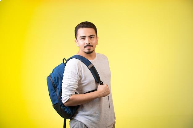 Mężczyzna Trzyma Niebieski Plecak I Wygląda Zalotnie. Darmowe Zdjęcia