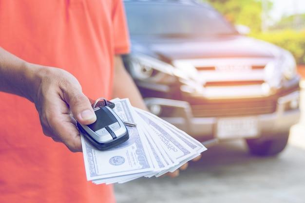 Mężczyzna Trzyma Samochodowych Klucze I Dolary Z Samochodem Premium Zdjęcia