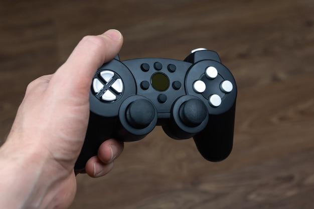 Mężczyzna Trzyma W Ręku Bezprzewodowy Gamepad Z Konsoli Do Gier Wideo Premium Zdjęcia