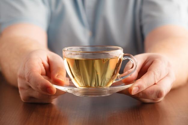 Mężczyzna Trzyma W Ręku Filiżankę I Oferuje Herbatę Premium Zdjęcia