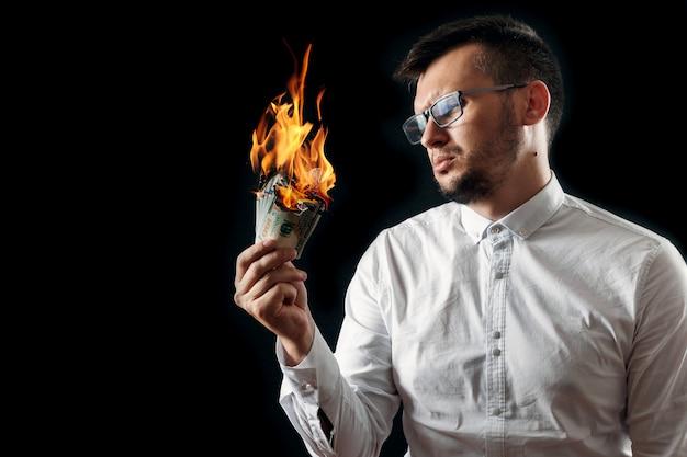 Mężczyzna trzyma w ręku płonące pieniądze Premium Zdjęcia