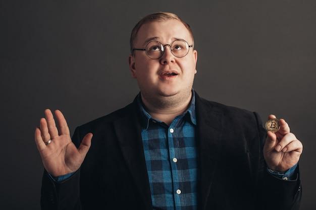 Mężczyzna Trzyma W Ręku Symbol Bitcoin Kryptowaluty I Mówi Bogu Dzięki Premium Zdjęcia