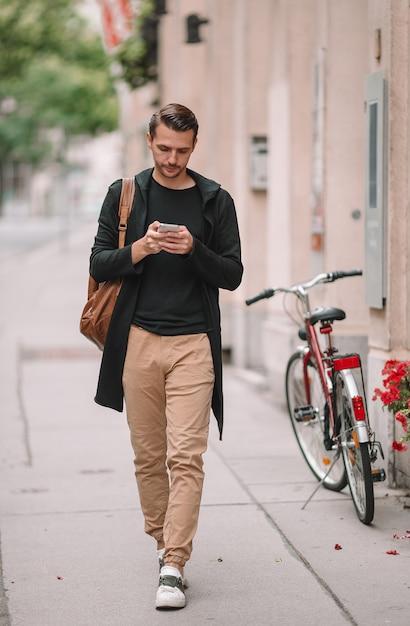 Mężczyzna turysta z plecakiem w europie ulicy. kaukaski chłopiec patrząc z mapą europejskiego miasta. Premium Zdjęcia