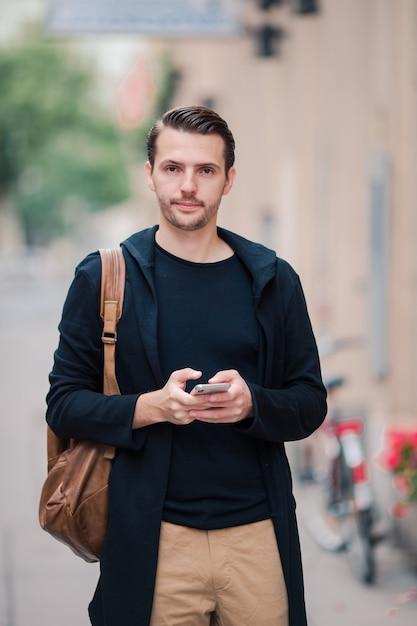 Mężczyzna turystyczny z mapą miasta i plecakiem na ulicy europy. kaukaski chłopiec patrząc z mapą europejskiego miasta. Premium Zdjęcia