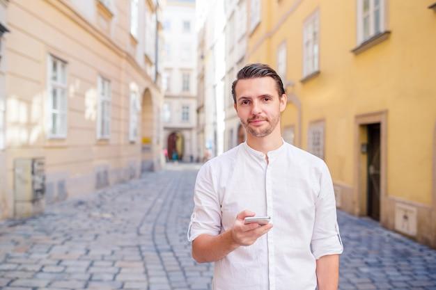 Mężczyzna turystyczny z mapą miasta i plecakiem na ulicy europy. Premium Zdjęcia