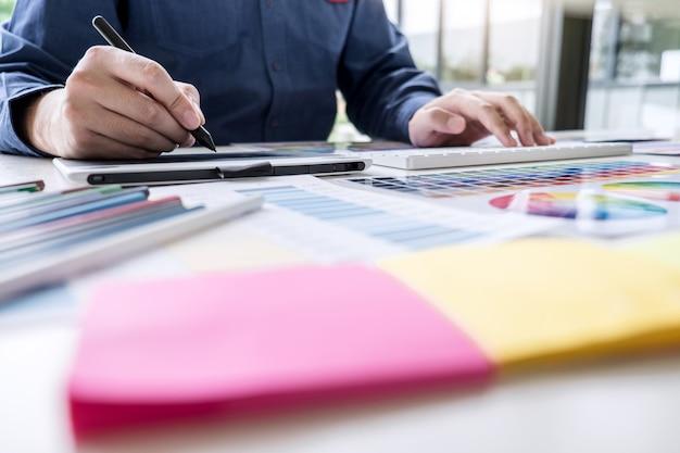 Mężczyzna twórczy grafik pracujący nad wyborem kolorów i próbkami kolorów, rysując na tablecie graficznym w miejscu pracy z narzędziami roboczymi i akcesoriami Premium Zdjęcia