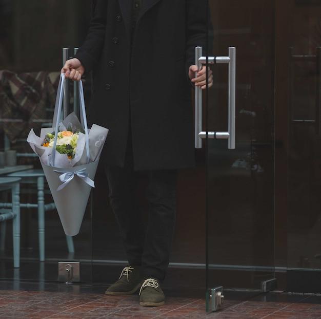 Mężczyzna ubrany na czarno, z białym bukietem kwiatów Darmowe Zdjęcia