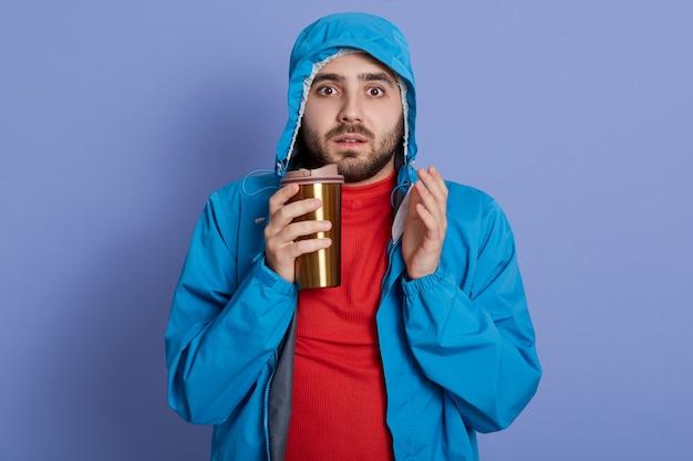 Mężczyzna Ubrany W Kurtkę I Czerwoną Koszulę Pije Kawę Przed Niebieską ścianą, Patrząc Prosto W Kamerę Z Zadziwionym Wyrazem Twarzy Darmowe Zdjęcia