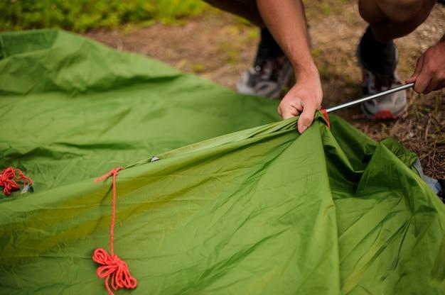 Mężczyzna Ustawia Zielony Namiot W Metalowej Ramie Premium Zdjęcia