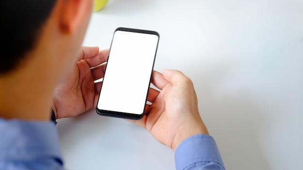 Mężczyzna używa smartphone makieta z pustym ekranem. Premium Zdjęcia