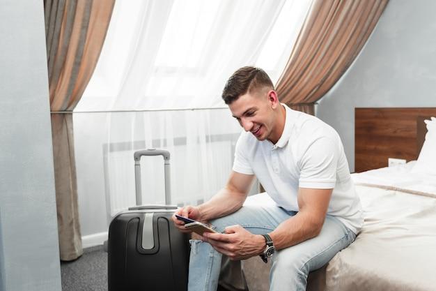 Mężczyzna Używa Smartphone W Pokoju Hotelowym Premium Zdjęcia
