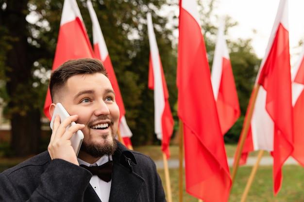 Mężczyzna Używa Smartphone Z Flaga Polska Behind Premium Zdjęcia