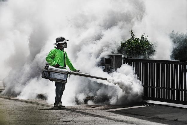 Mężczyzna używa zamgławiającej maszyny do kontrolowania niebezpiecznego od komarów Premium Zdjęcia