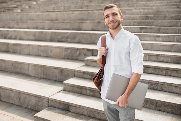 Mężczyzna w białej koszuli trzyma laptopa i uśmiecha się do kamery Darmowe Zdjęcia