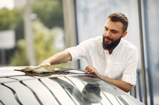 Mężczyzna W Białej Koszuli Wyciera Samochód W Myjni Samochodowej Darmowe Zdjęcia