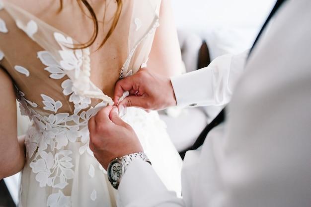 Mężczyzna W Białej Koszuli Z Krawatem I Zegarkiem Zapina Guziki Gorsetu Sukienki. Panna Młoda W Sukni ślubnej Z Koronką Stojącą W Pokoju. Premium Zdjęcia