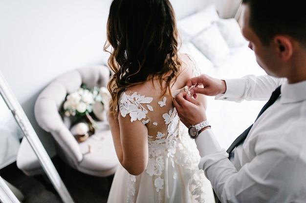 Mężczyzna W Białej Koszuli Z Krawatem I Zegarkiem Zapina Guziki Gorsetu Sukienki. Panna Młoda W Sukni ślubnej Z Koronki Stojącej W Domu. Premium Zdjęcia