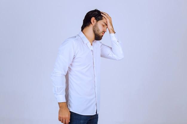Mężczyzna W Białej Koszuli Zasłania Twarz, Czuje Się Smutny I Boli Go Głowa. Darmowe Zdjęcia