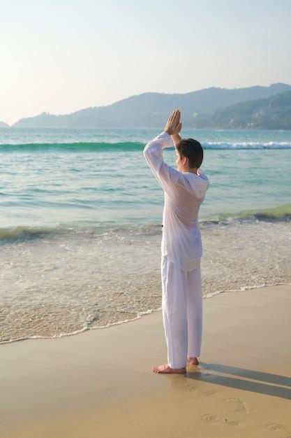Mężczyzna W Białym Ubraniu Trzyma Ręce W Geście Modlitwy I Praktykuje Medytację Jogi Premium Zdjęcia