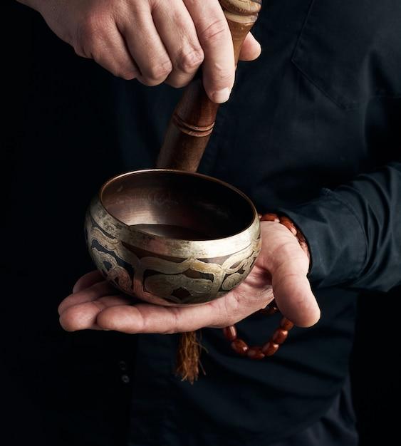 Mężczyzna W Czarnej Koszuli Obraca Drewniany Kij Wokół Miedzianej Misy Tybetańskiej Premium Zdjęcia