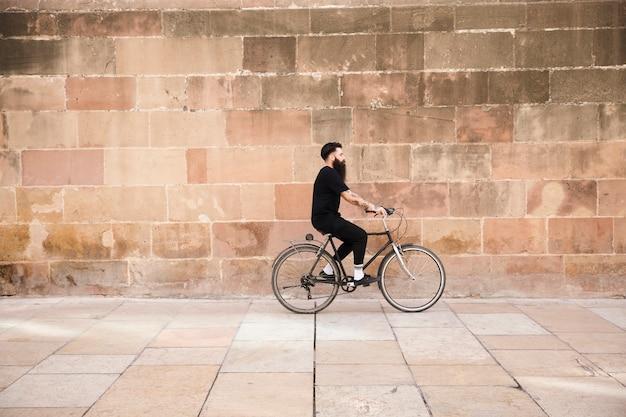 Mężczyzna w czarnej odzieży jedzie na rowerze przed ścianą Darmowe Zdjęcia