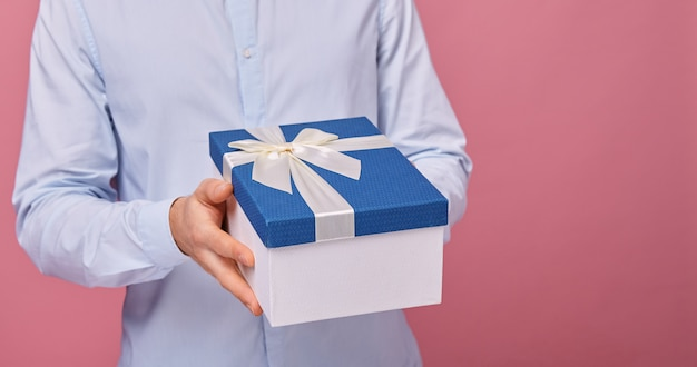 Mężczyzna w delikatnie niebieskiej koszuli ma prezent Premium Zdjęcia