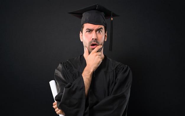 Mężczyzna W Dniu Ukończenia Uniwersytetu Zaskoczony I Zszokowany, Gdy Patrzy W Prawo Premium Zdjęcia