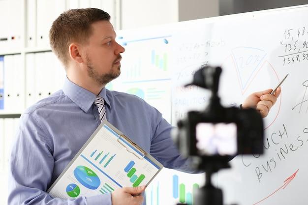 Mężczyzna W Garniturze I Pod Krawatem Pokazuje Wykresy Statystyk Premium Zdjęcia
