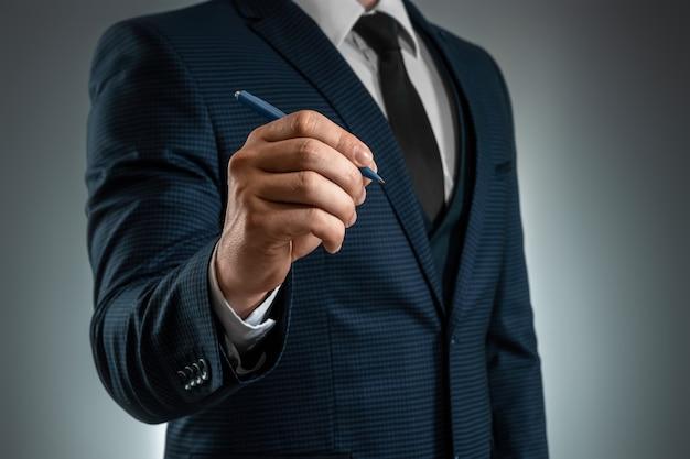 Mężczyzna W Garniturze Wyciąga Rękę Długopisem, Pisze W Powietrzu. Zdjęcie Dla Koncepcji Biznesowej. Close-up, Kopia Przestrzeń. Premium Zdjęcia