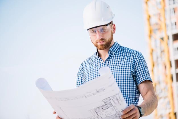 Mężczyzna W Hardhat Patrzeje Projekta Papier Premium Zdjęcia
