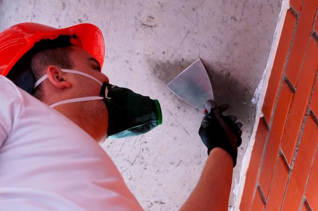 Mężczyzna w hełmie i respiratorze wykonuje prace malarskie na betonowym suficie, na tle muru. Premium Zdjęcia