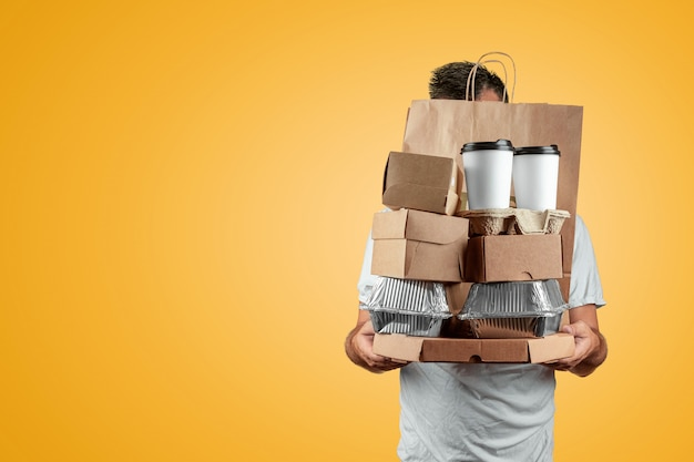 Mężczyzna W Jasnej Koszulce, Podając Zamówienie Typu Fast Food Na Białym Tle Na żółtym Tle Premium Zdjęcia