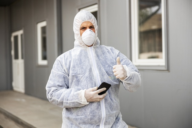 Mężczyzna W Kombinezonie I Masce Chroniącej Przed Wirusami Patrzy I Pisze Na Smartfonie Telefonu Komórkowego, Dezynfekuje Budynki Koronawirusa Opryskiwaczem Premium Zdjęcia