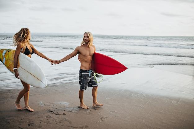 Mężczyzna W Krótkich Spodenkach I Dziewczyna W Stroju Kąpielowym, Trzymając Się Za Ręce. Para Idzie Surfować Darmowe Zdjęcia