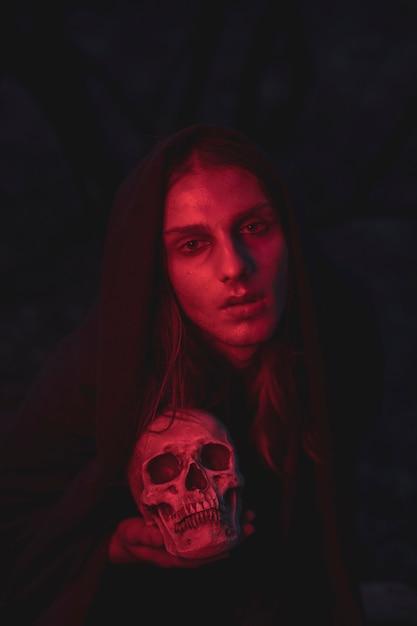 Mężczyzna w odcieniach czerwonego światła siedzi w ciemności z czaszką Darmowe Zdjęcia