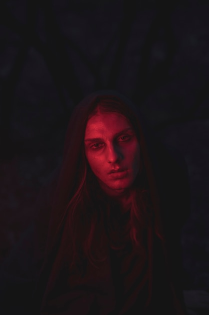 Mężczyzna w odcieniach czerwonego światła siedzi w ciemności Darmowe Zdjęcia