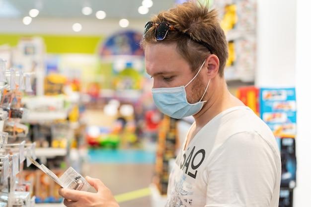 Mężczyzna W Sklepie Nosi Maskę Ochronną. Bezpieczeństwo, Ochrona Zdrowia Podczas Kwarantanny Covid-19. Premium Zdjęcia