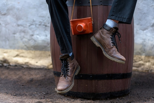 Mężczyzna W Skórzanych Butach Siedzi Na Drewnianej Beczce I Trzyma Rocznika Filmowego Aparatu Premium Zdjęcia