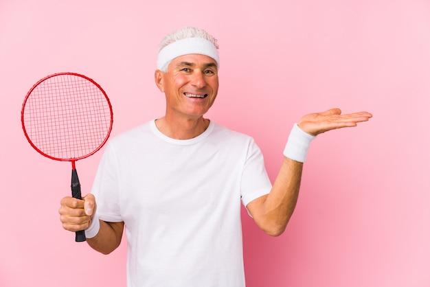 Mężczyzna W średnim Wieku, Grając W Badmintona, Pokazując Kopię Miejsca Na Dłoni I Trzymając Inną Rękę Na Talii. Premium Zdjęcia