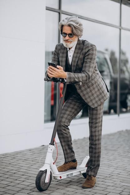 Mężczyzna W średnim Wieku Jedzie Skuter W Klasycznym Garniturze Darmowe Zdjęcia