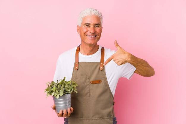 Mężczyzna W średnim Wieku Ogrodnik Na Białym Tle Osoba Wskazująca Ręką Na Koszulkę, Dumny I Pewny Siebie Premium Zdjęcia