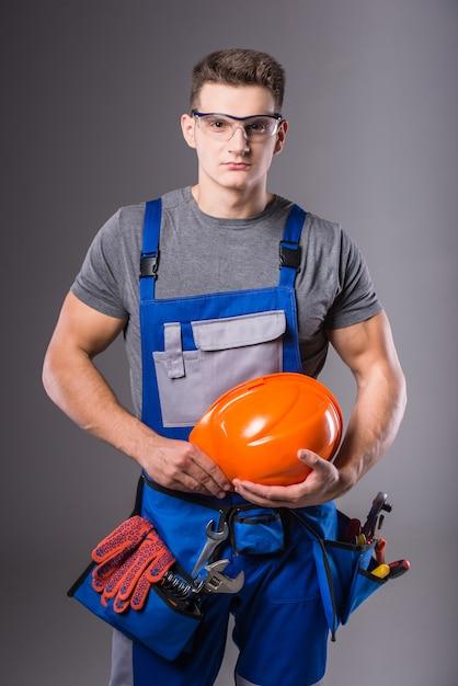 Mężczyzna w stroju stoi z hełmem w dłoniach. Premium Zdjęcia