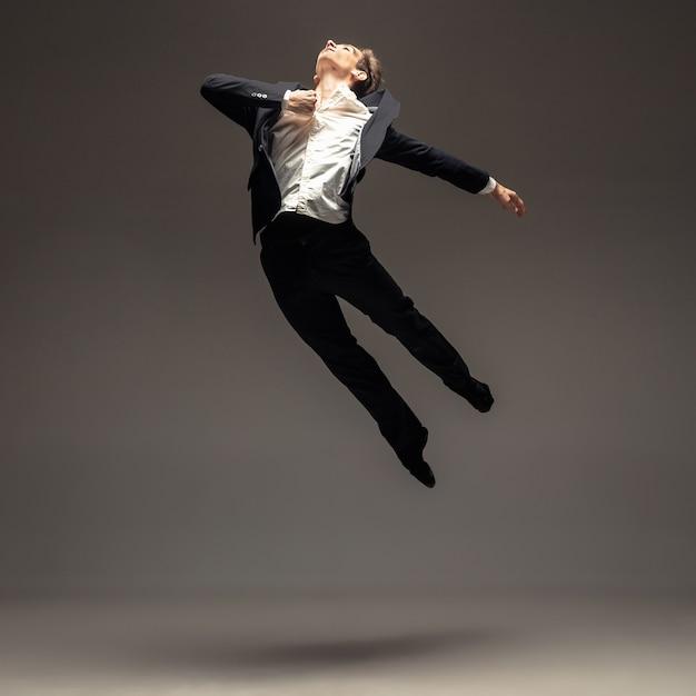 Mężczyzna W Ubranie W Stylu Casual, Biuro Skoki I Taniec Na Szarym Tle Darmowe Zdjęcia