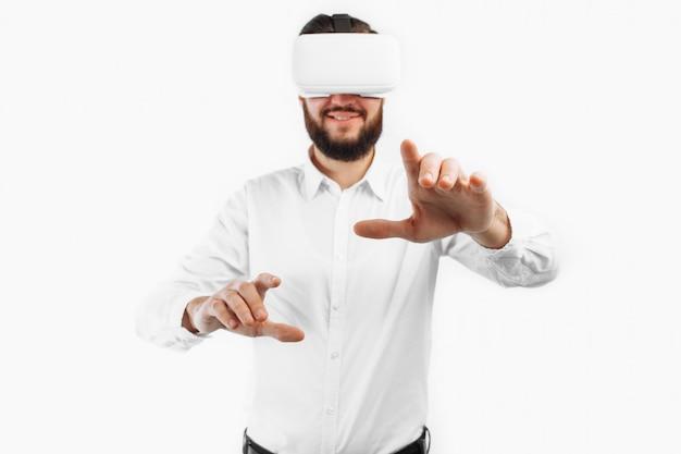 Mężczyzna W Wirtualnych Okularach Naciska Palec Na Pustą Przestrzeń Na Białej ścianie Premium Zdjęcia