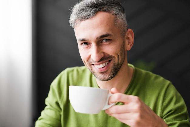 Mężczyzna W Zielonej Koszuli Uśmiecha Się I Przytrzymaj Filiżankę Kawy Darmowe Zdjęcia