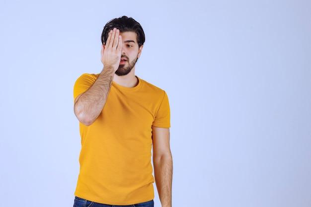 Mężczyzna W żółtej Koszuli Patrząc Przez Palce. Darmowe Zdjęcia
